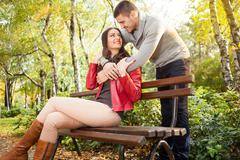 Couple enjoying golden autumn fall season in park Stock Photos