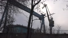 Behind the fence shipbuilding cranes in the port behind the trees, morning Stock Footage