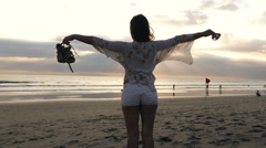 Woman with wide open arms enjoying sunset on beach Stock Footage