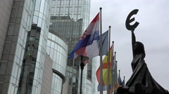 European Parliament in Brussels, Euro symbol statue, flags and modern building Stock Footage