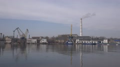 Thick smoke coming from large pipe on background of shipyard with ships, slipway Stock Footage