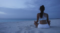 Meditation - Yoga woman meditating at serene beach in lotus pose Stock Footage