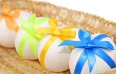 Easter eggs decorated with bows in a basket - stock photo