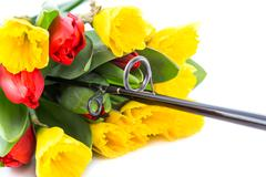 Fishing rod with bouquet spring flowers Stock Photos