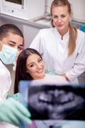 Dentist explaining the details of x-ray picture to his patient - stock photo
