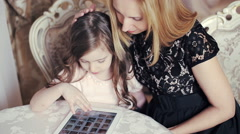 Mother and daughter looking photos of  tablet - stock footage