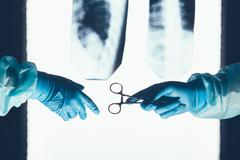Two surgeons working and passing surgical equipment in the operating room Stock Photos
