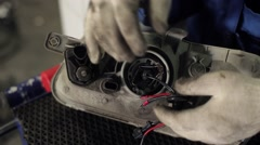 Installing xenon lamp on car in auto service Stock Footage