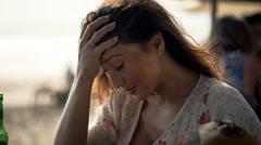 Sad, unhappy woman sitting in beach bar - stock footage