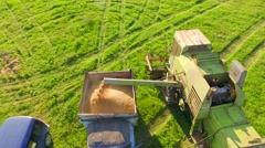 AERIAL VIEW. Combine Harvester Unloading Wheat Grain Into The Tractor Trailer Stock Footage