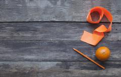 Tangerines with pencil and orange ribbon on old wooden table wit - stock photo