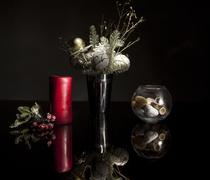 Candle and Christmas decorations on a glass table - stock photo