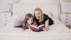 happy woman reading a book to her cute daughter - stock footage