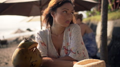 Woman waiting for someone and drinking coconut cocktail in beach bar Stock Footage