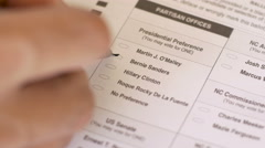 Hand filling in voting ballot for Bernie Sanders in the 2016 primary close up Stock Footage