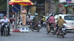 Female police officer guiding traffic during rush hour in Hanoi, Vietnam Stock Footage