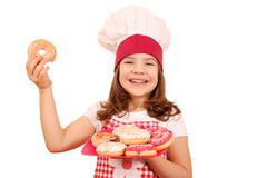 Happy little girl cook with sweet donuts Stock Photos