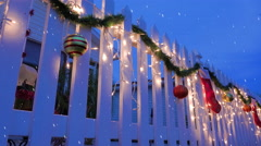 Snowing on Christmas decorated picket fence at dusk Stock Footage