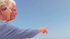 Senior couple pointing in the blue sky Stock Footage