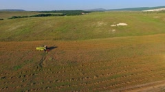 AERIAL VIEW. Farm Machinery Cutting Field At Harvest Stock Footage