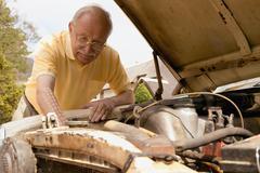 Senior man looking at car engine Kuvituskuvat