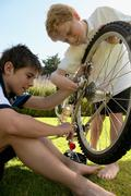 Young boys mending bicycle - stock photo