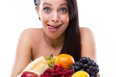 Funny young woman is crazy about fresh fruits Stock Photos