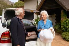 Senior couple arriving by car Stock Photos