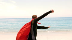 Man in wet suit dressed as superman Stock Footage