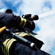 Fireman operating hose Stock Photos