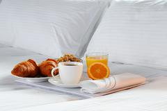 Breakfast in bed in hotel room. Accommodation. Stock Photos