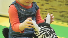 Child is ridden on a toy zebra - stock footage