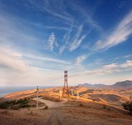 High voltage tower in mountains at sunset. Electricity pylon system - stock photo