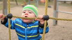 Baby is biting a rope on the playground  Stock Footage