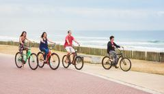 Ordinary family riding bicycles together on the promenade - stock photo