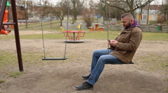 Man writing a message and swinging on the playground  Stock Footage