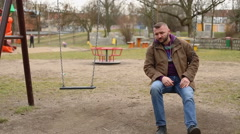 Sad man swinging and thinking about something - stock footage