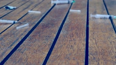 Camera slides above wooden surface, shows several syringes Stock Footage