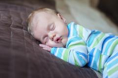 Stock Photo of Little baby sleeping on the bed in room