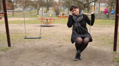 Really sad female swinging on swing on the  playground  - stock footage