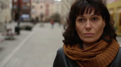 Sad and tired woman looks around in the city centre Stock Footage