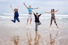 Happy family jumping together on the beach in landscape - stock photo