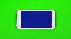 Smartphone lying on green screen, finger presses blue screen - stock footage