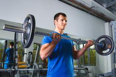Athlete muscular bodybuilder in the gym training with bar Stock Photos