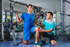 Stock Photo of sport, fitness, teamwork, bodybuilding people concept - man and personal trainer