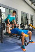 Young Man In Gym Exercising Chest On The Bench Press with barbell Stock Photos