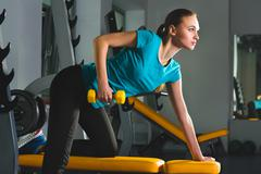 Stock Photo of Fitness sporty young sexy Woman in gym doing exercises with dumbbells