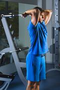 Young Athlete Exercise In The Gym - He Is Performing Triceps Exercises - stock photo