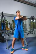 sport, bodybuilding, lifestyle and people concept - young man with barbell doing - stock photo