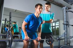 Muscular Man Lifting Deadlift In The Gym with instructor - stock photo